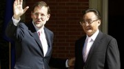 Spanish Prime Minister Rajoy waves beside the Chairman of China's National People's Congress Wu Bangguo before their meeting in Madrid