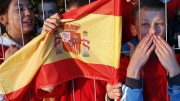 Local fans hold a Spain flag as the Spanish soccer team arrive at their training base in Gniewino