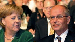 German chancellor Angela Merkel speaks with IG Metall trade union's head Berthold Huber