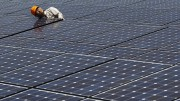 File photo of a worker checking solar panels at a solar power field in Kawasaki, near Tokyo