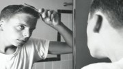 Rear view of a teenage boy combing his hair in front of a mirror, 1960