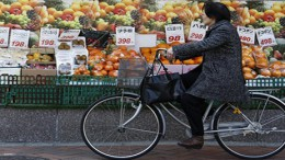 A woman rides a bicycle past outside a food store in Tokyo