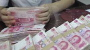 An employee counts Chinese 100 yuan banknotes at a branch of Bank of Communications in Shenyang