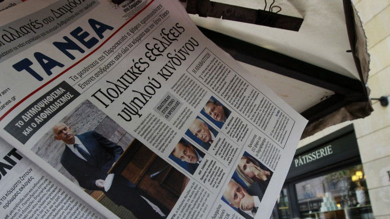 A woman walks past Greek newspapers bearing cover photos of Greek Premier George Papandreou in Athens