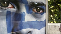 A man walks past a pre-election poster of the Democratic Alliance party at a bus station in Athens