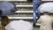 Menschen mit Regenschirmen gehen eine Treppe hinauf.